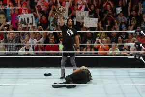 Seth Rollins proudly standing over Roman Reigns after his pedigree surprise return.