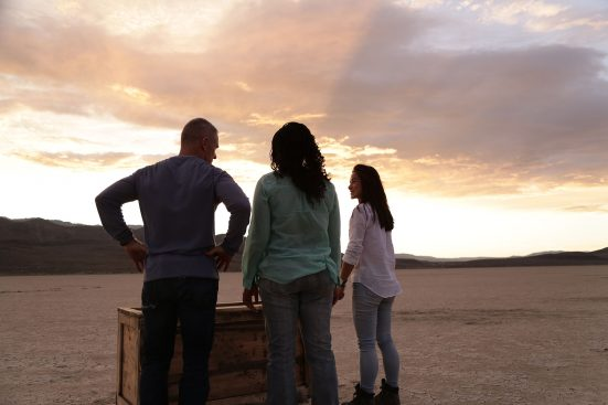 Genius with Stephen Hawking.BLACK ROCK DESERT, NEV. - Volunteers; James Fitzsimmons, Joy Ng and CaTamira Babino, looking inside a crate for a clue to the next demo.