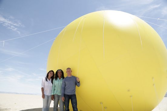 Genius with Stephen Hawking.BLACK ROCK DESERT, NEV. - Volunteers; James Fitzsimmons, Joy Ng and CaTamira Babino stand next to a replica of the sun.