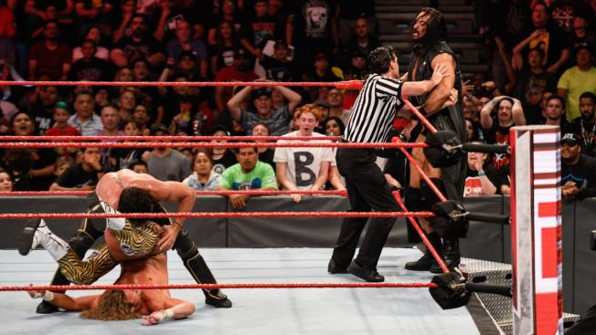 Seth Rollins rolls up Dolph Ziggler while Drew McIntyre distracts the ref