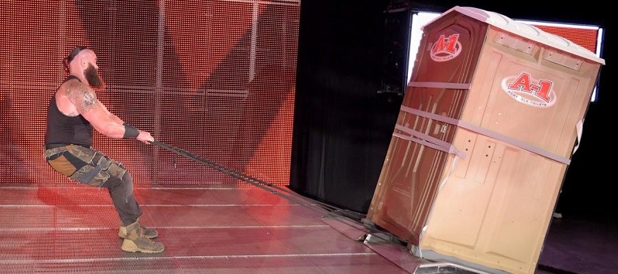 Braun Strowman drags a porta-potty across the stage with Kevin Owens inside
