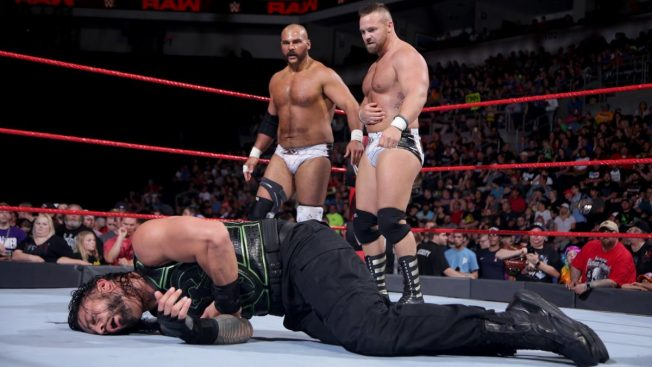 The Revival stand over Roman Reigns