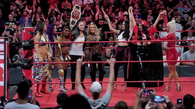 Ronda Rousey in the ring with the Bellas, Natalya, Dana Brooke, Sasha Banks, Bayley, and Ember Moon