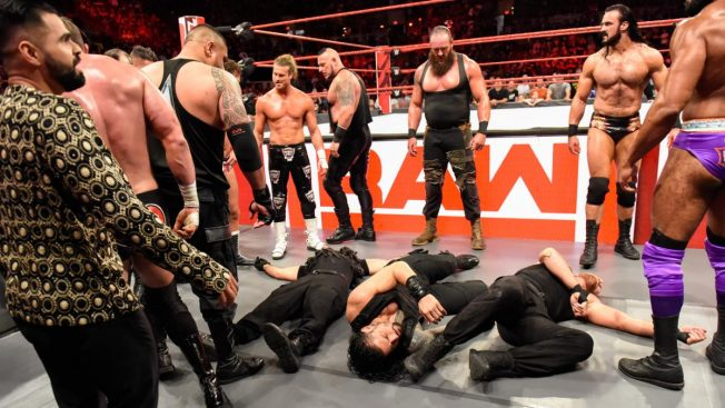The Shield laid out at ringlide surrounded by the locker room with Ziggler, McIntyre, and Strowman looking on