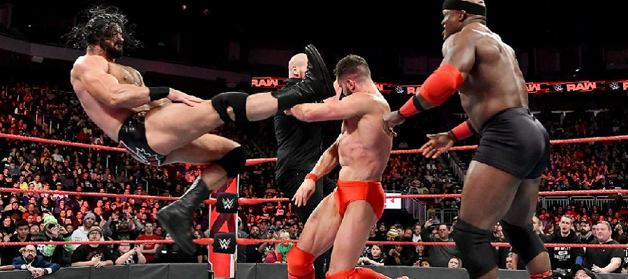 Bobby Lashley and Baron Corbin hold Finn Balor up to take a Claymore
