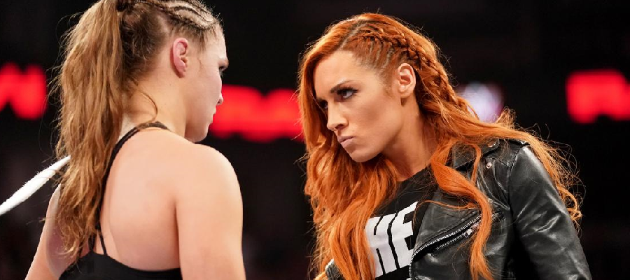 Becky Lynch and Ronda Rousey stare down.