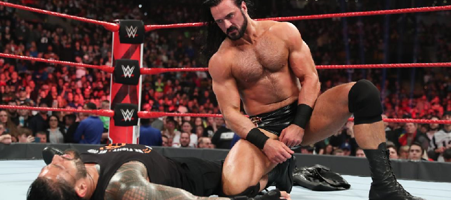 Drew McIntyre kneels over Roman Reigns