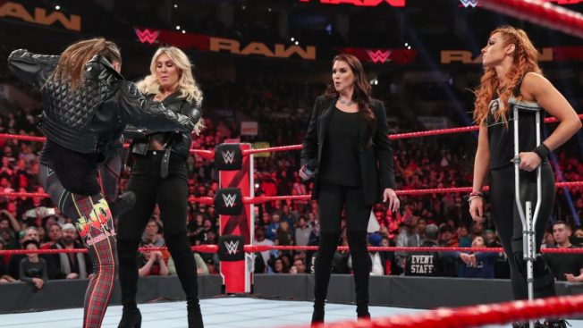 Ronda Rousey kicks Charlotte Flair while Stephanie McMahon and Becky Lynch stand looking