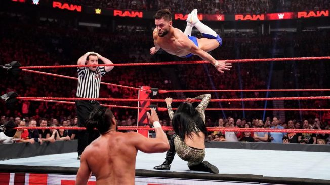 Finn Balor flies over Velina Vega onto Andrade while the ref looks shocked