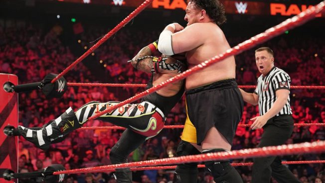 Samoa Joe attempts to put the Coquina Clutch on Rey Mysterio