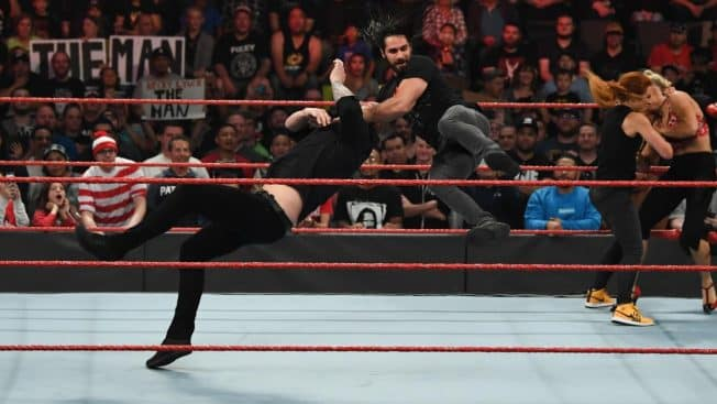 Seth Rollins slingblades Baron Corbin while Becky Lynch beats on Lacey Evans
