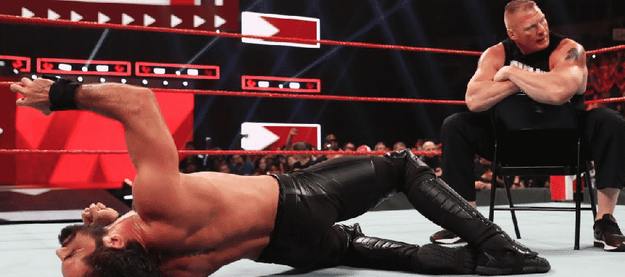 Seth Rollins laying on the mat with Brock Lesnar sat on the chair her just hit him with