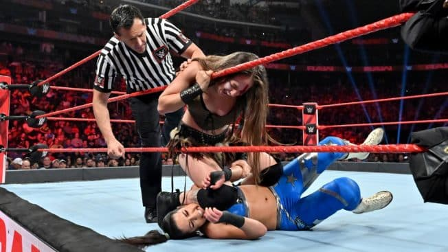 Sarah Logan with her knee on Bayley's head