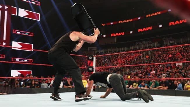 Brock Lesnar hits Seth Rollins with a chair