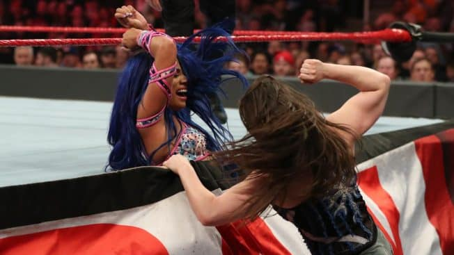 Nikki Cross with Sasha Banks tied in the ring skirt