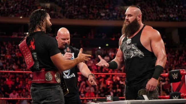 Rollins and Strowman about to shake hands over the contract, with Stone Cole Steve Austin in the background