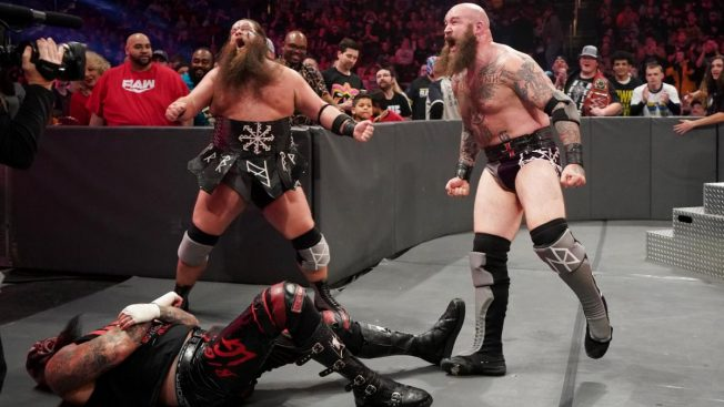 The Viking Raider stand over Luke Gallows at ringside