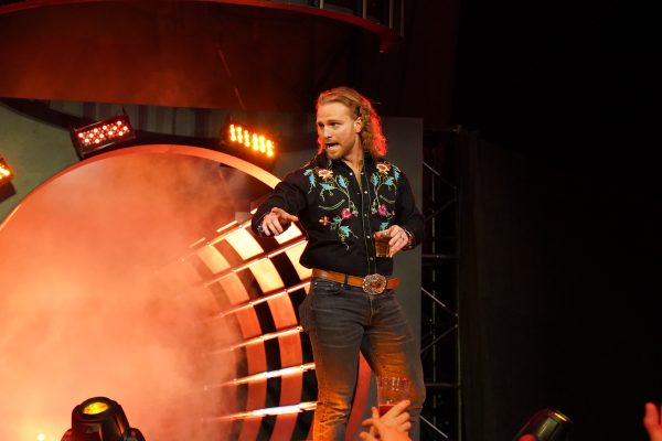 Hangman Adam Page enjoys an alcoholic beverage on the way to the commentary desk